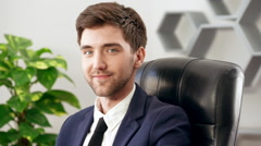 Young successful businessman showing okay, smiling at his workplace in office Stock Footage