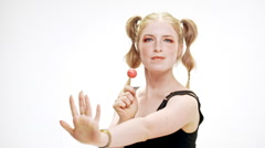 Young beautiful girl dancing, smiling, holding chupa chups over white background Stock Footage