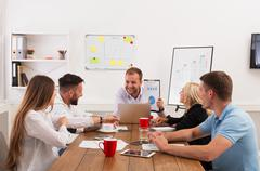Business meeting. Young hipsters businessmen and women at modern office - stock photo