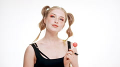 Young beautiful girl smiling, holding chupa chups over white background. Slow Stock Footage