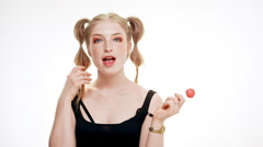 Young beautiful girl smiling, winking, holding chupa chups over white background Stock Footage
