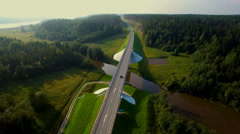 Aerial view of cars going over the bridge in the forest Stock Footage