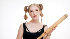 Young beautiful girl looking at camera brutally, holding bat over white Stock Footage