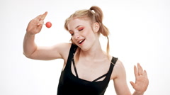 Young beautiful girl dancing, smiling, holding chupa chups, singing over white Stock Footage
