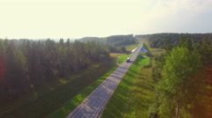 Beautiful aerial view of the truck coming down the road in the woods. Arkistovideo