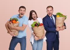 Happy people hold bags with healthy food, grocery buyers isolated Kuvituskuvat
