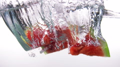 Fresh ripe watermelon slices falls into water with splashes on white background Stock Footage