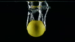Slow motion fresh lemon falling in the splashes of water on black background Stock Footage
