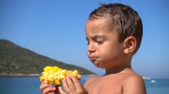 Kid chews and looks at corn - stock footage