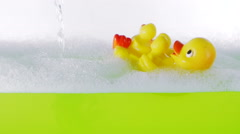 Yellow rubber duck floating in bathtub with soapy water and green sea bath salt Stock Footage