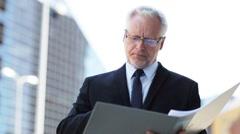 senior businessman with ring binder folder in city - stock footage