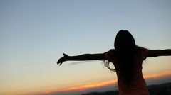 Silhouette of young woman raising hands to sun at sunset. Moment of freedom and Stock Footage
