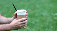 MAN GIVES TO GIRLFRIEND CUP OF COFEE GREEN GRASS LVIV UKRAINE Stock Footage