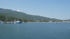Seascape of settlement under hills with boats in the port by Sheyno. - stock footage