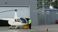 Ground crew member prepare a helicopter for departure Stock Footage