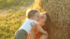 Kid in the white shirt sitting c young mother in a white dress near a haystack Stock Footage