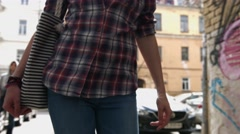 Woman in a checkered shirt, blue jeans and bag walking on the street, concept of Stock Footage
