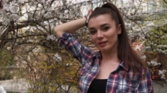 Beautiful brunette woman wearing checkered shirt in the park playing with hair Stock Footage
