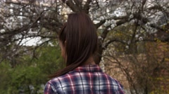 Beautiful young smiling brunette woman in checkered shirt standing near the Stock Footage