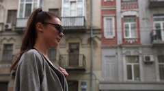 Attractive well dressed in gray coat and blue jeans young woman walking across - stock footage