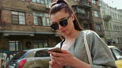 Beautiful brunette girl in sunglasses holding a smart phone, messages, posting Stock Footage