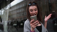 Delighted young woman reading asms on her mobile phone smiling with excitement Stock Footage