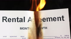 Closeup of white sheet of paper with text rental agreement burning in fire Stock Footage