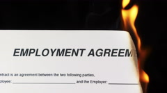 Closeup of white sheet of paper with text employment agreement burning in fire Stock Footage