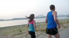 Couple of young adult athletes: woman and man running along promenade of river Stock Footage