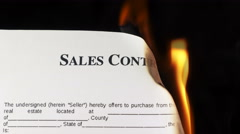 Closeup of white sheet of paper with text sales contract burning in fire Stock Footage