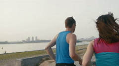 Couple of young adult athletes: woman and man running along promenade of river Arkistovideo