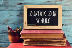 Text back to school in German in a chalkboard Stock Photos