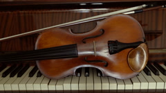 Violin with bow lying on the piano keys. Still life of violin and piano Stock Footage