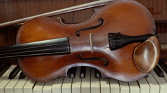 Violin lying on the piano keys. Close uo slider shot Stock Footage