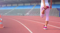 Young woman warming-up at stadium Stock Footage