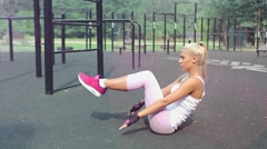 Young attractive blonde woman doing sport exercises outdoors Stock Footage