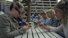 Wide shot of a group of girls sitting at a park bench all using their iPhones Stock Footage