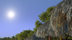 Tropical beach scene with a moving sunshade and blue sky Stock Footage