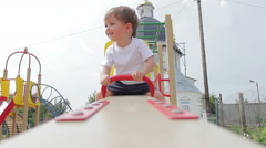 Boy kid swinging up and down on a playground swing Stock Footage