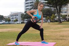 An attractive female exercising in the outdoors with a kettlebell weight whil Stock Photos