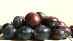 Hand picking up plums with copy space on white background - stock footage