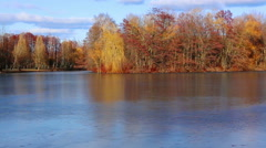 River covered with ice and autumn trees on the other side - stock footage