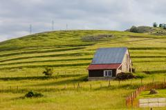 Idyllic scene of rural house on the green hill at summer morning. - stock photo
