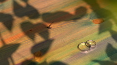 wedding rings lie on a wooden surface - stock footage