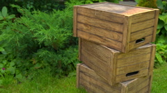 Wooden boxes lie on the grass on a background of green bushes Stock Footage
