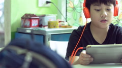 Dolly shot of a asian preteens in headphones using tablet computer indoor. Stock Footage