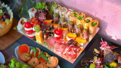 Beautifully decorated buffet table, canapés, rolls, vegetables, fish Stock Footage