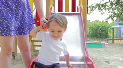 Little boy on the playground goes from top to bottom Stock Footage