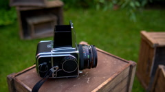 camera Hasselblad lies on a wooden box on a grass background - stock footage