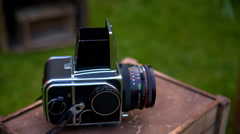old large format camera lying on a wooden box on a grass background - stock footage